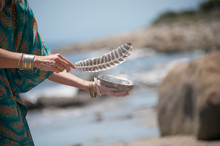 Woman Hands Holding A Feather And Seashell With Sage Smudge.