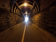 Bright Light At The End Of A Tunnel With Trail And Bricks And Person