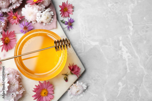 Flat lay composition with jar of organic honey and dipper on grey marble table. Space for text