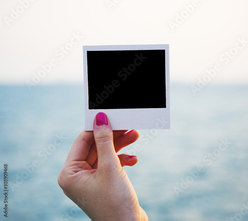 Closeup of woman's hand holding blank black photograph with copy space to horizon with sea blurred/bokeh background/backdrop. Insert your own content. Wall mural
