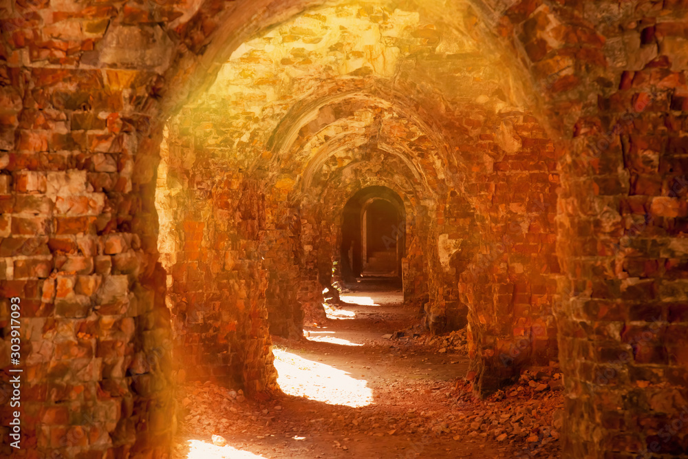 Fototapeta Ruins of an ancient medieval ruined castle in sun rays. Arch background.