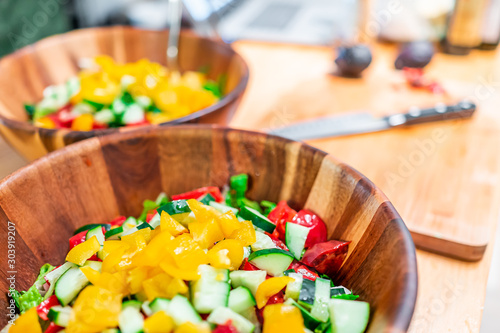 Chopped colorful vegetables in two wooden vegan salad bowls with cucumbers and yellow bell peppers and blurry background of empty cutting board