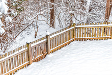 Wooden Backyard Fence Of House With Trees Forest In Neighborhood With Snow Covered Ground During Blizzard White Storm Snowflakes And Small Gate Door