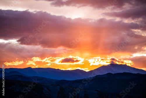 Fotografía Orange purple cloudy sunset sun rays in Aspen, Colorado with rocky mountains pea