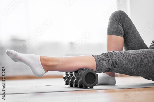Fotografía  Young woman doing yoga while lying on massager on rug on wooden floor against ba