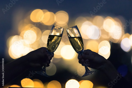 Foto auf Leinwand Alkohol Cheers and celebration with champagne alcoholic drinks and beautiful golden city lights.