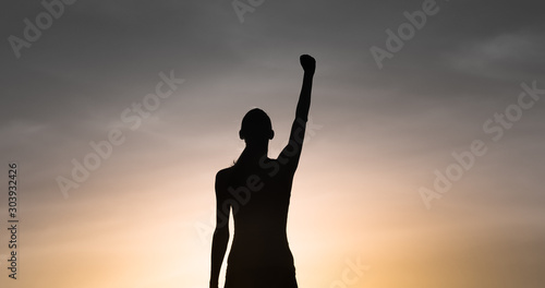 Valokuva Strong determined female with hand raised to the sky
