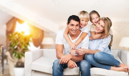 Canvastavla  Young family at home smiling at camera