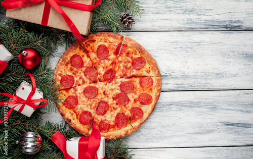 Christmas pepperoni pizza with Christmas decorations, gift, spruce, toys