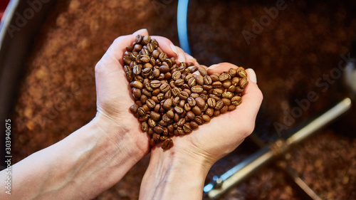 Obraz close-up view of roasted coffee beans in hand - fototapety do salonu