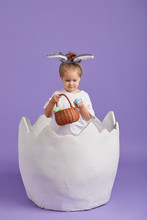 Happy Child Girl In Costume Easter Bunny Rabbit With Ears And A Basket With Eggs. Little Girl In A Big Chicken Egg On A Purple Background