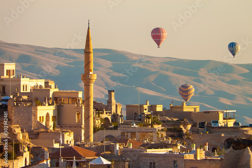 Obraz na płótnie Baloons ascending at  sunrise over minaret and buildings of Cappadocia, Turkey,