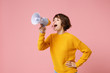 Leinwandbild Motiv Funny young brunette woman girl in yellow sweater posing isolated on pastel pink wall background studio portrait. People sincere emotions lifestyle concept. Mock up copy space. Screaming in megaphone.