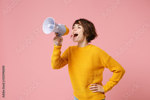Billede på lærred Funny young brunette woman girl in yellow sweater posing isolated on pastel pink wall background studio portrait