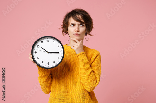 Obraz Pensive young brunette woman girl in yellow sweater posing isolated on pastel pink background, studio portrait. People lifestyle concept. Mock up copy space. Holding clock, put hand prop up on chin. - fototapety do salonu