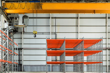 Yellow Overhead Crane In Industrial Warehouse Building With Rows Of Racks