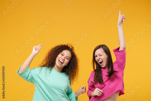 Obraz Two cheerful women friends european african american girls in pink green clothes posing isolated on yellow background. People lifestyle concept. Mock up copy space. Having fun dancing rising hands up. - fototapety do salonu