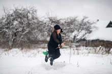 Excited Girl Dressed In With Costume Starting To Gly On Her Broomstick To Coven In Snowy Winter Day In Countryside Nature.