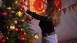 Young woman decorate a christmas tree with toys. Gold presents. Domestic festive decor