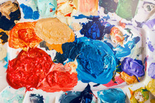 Beautiful Colorful Textured Paints Background. Paint Strokes And Left Overs Residues Of Paints In Palette Colour Array On Table. Colored Spots And Blotches Stains. View From Top Above.