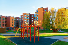 Apartment Residential House Facade Architecture With Children Playground And Outdoor Facilities. Blue Sky On The Background.