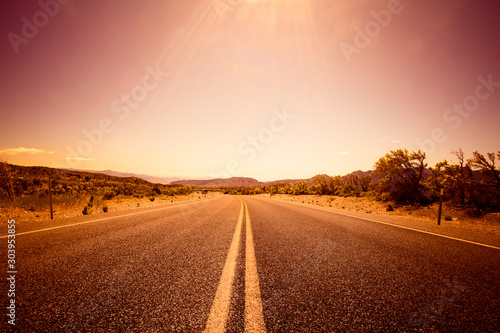 Foto auf Leinwand Braun Desolate desert road with mountains with sunflare; western United Stated