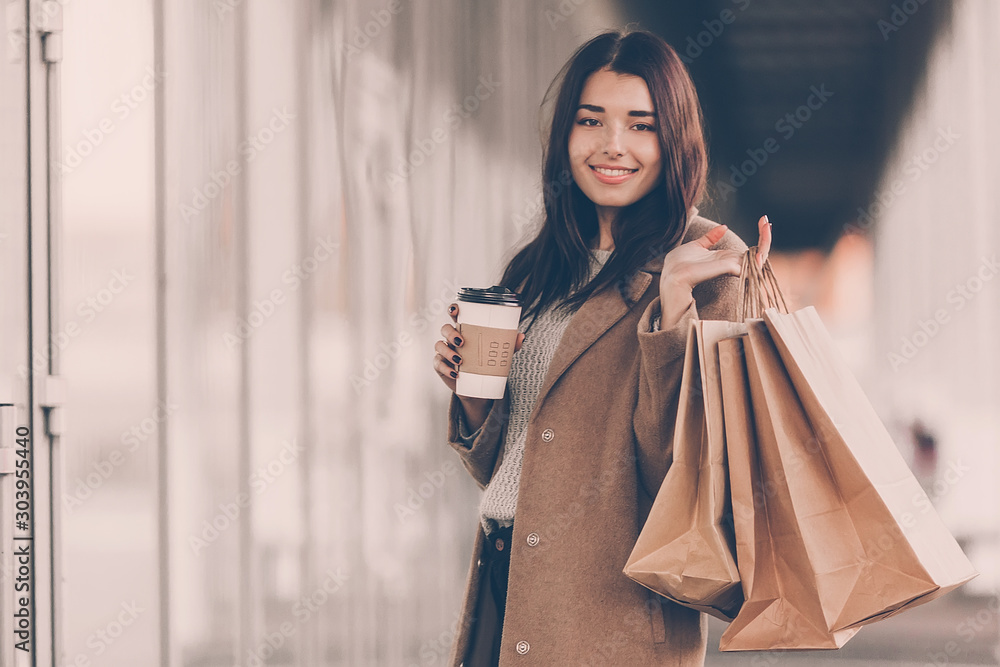 Fototapeta Beautiful fashionable woman with shopping bags and coffee walking near mall.