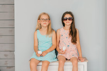 Two Fashionable Model Girls In Sunglasses And Zephyr In Hands Siiting On Dresser Over Gray Wall On Background.