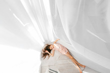 Portrait From Above Of Little Beautiful Girl With Long Hair Lying On Floor With White Curtain  Covering Her