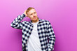 canvas print picture - young blonde man with squared shirt feeling puzzled and confused, scratching head and looking to the side