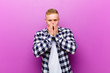 canvas print picture - young blonde man with squared shirt looking happy, cheerful, lucky and surprised covering mouth with both hands