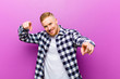 Leinwanddruck Bild - young blonde man with squared shirt feeling happy and confident, pointing to camera with both hands and laughing, choosing you