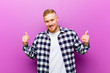 canvas print picture - young blonde man with squared shirt smiling joyfully and looking happy, feeling carefree and positive with both thumbs up