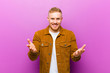 canvas print picture - young blonde man feeling happy, astonished, lucky and surprised, like saying omg seriously? Unbelievable against purple background