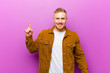 canvas print picture - young blonde man smiling cheerfully and happily, pointing upwards with one hand to copy space against purple background