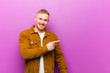 canvas print picture - young blonde man looking excited and surprised pointing to the side and upwards to copy space against purple background