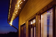 Cozy Scene Of String Lights Hanging Under The Roof At Evening Time. Christmas Party. Outdoor Electric Lamps