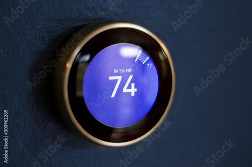 Fototapeta Blue screen round thermostat against a dark blue wall saving money with green tech obraz