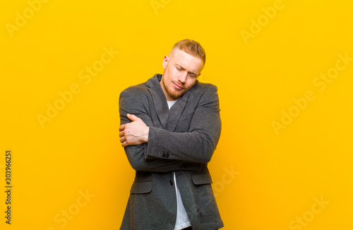 Fotografía  young blond businessman feeling in love, smiling, cuddling and hugging self, sta