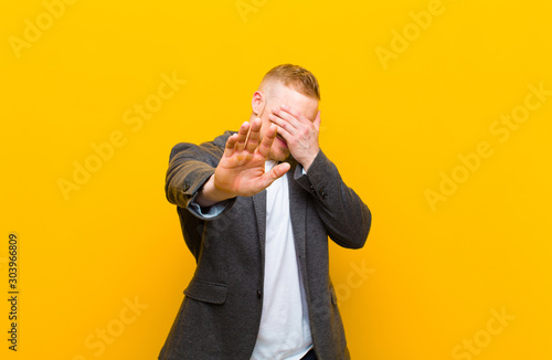 young blond businessman covering face with hand and putting other hand up front Fototapet