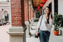 Tourist Asian Women Walking In Chinese Monument While Travel In Beijing China. Young Charming Lady Tourist Sightseeing Joyful In Corridor With Brick Pillar. Red Lantern Hanging On Ceiling In Walkway.