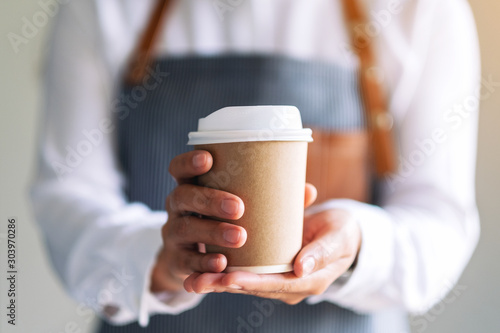 Fototapeta A waitress holding and serving a paper cup of hot coffee in cafe