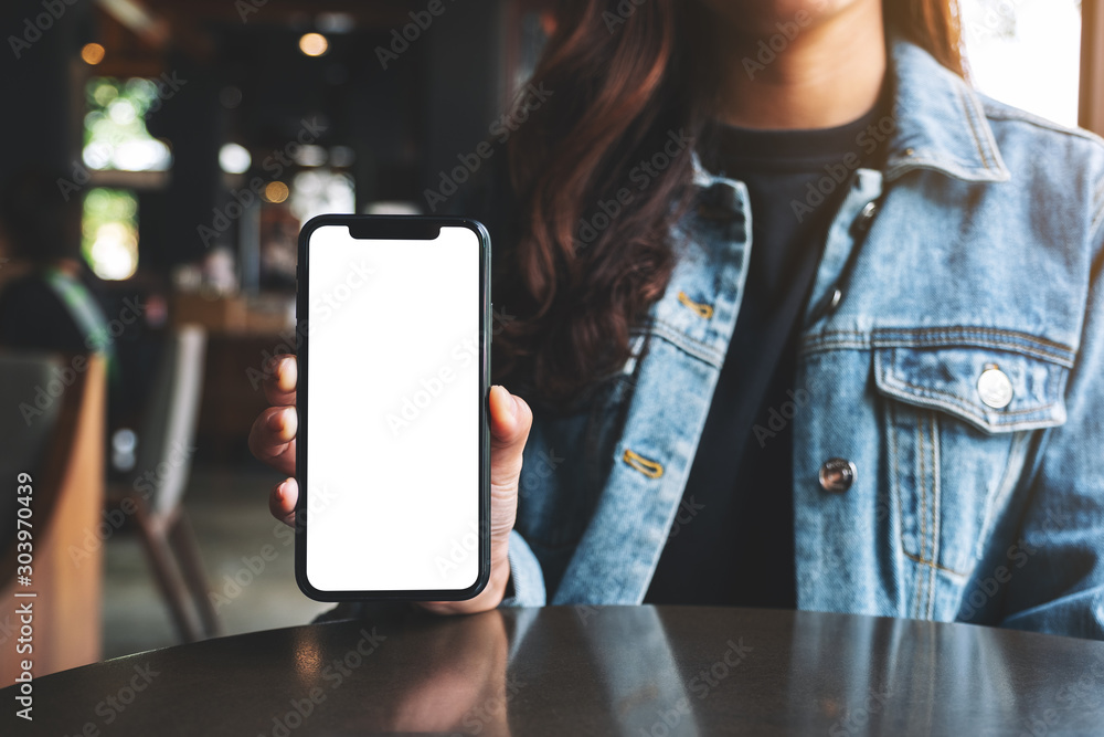 Obraz Mockup image of a woman holding and showing black mobile phone with blank screen in cafe fototapeta, plakat