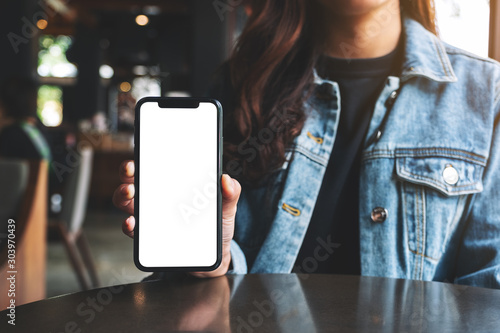 Obraz Mockup image of a woman holding and showing black mobile phone with blank screen in cafe - fototapety do salonu