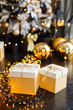 Christmas presents/gifts on black background with garland lights. Stylish New Year decoration. Golden gift boxes and balls under fir-tree on dark wooden floor. Christmas mood. Celebrating of New Year