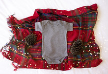Gray Blank Newborn Baby Bodysuit On A Tartan/plaid Christmas Background With Pine Cone Props