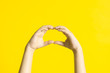 Leinwandbild Motiv Kid's hands with sign language on yellow background.