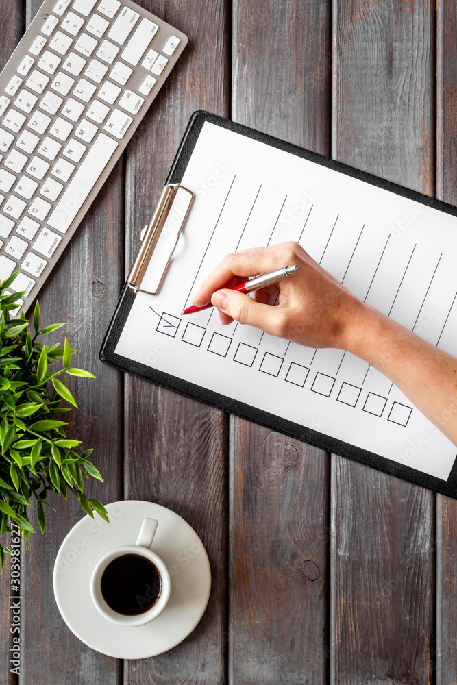 Fototapeta Hand fill checklist on dark wooden office background top view