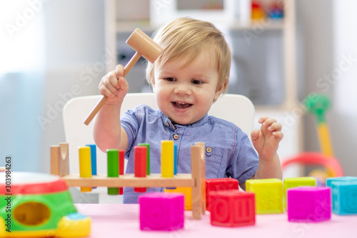 cute toddler baby boy playing with wooden hammer block toy