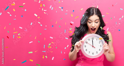 Canvastavla  Young woman holding a clock showing nearly 12